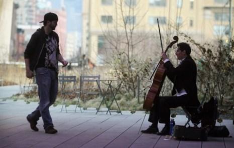 Прохожий подходит к уличному музыканту в парке Хай-Лайн, Нью-Йорк, чтобы отблагодарить его деньгами. Фото: Mario Tama/Getty Images