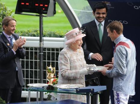 Королева Великобритании Елизавета II вручила главный приз жокею Ричарду Хьюзу на скачках в Аскоте (Англия) 19 октября 2013 года. Фото: Stuart C. Wilson/Getty Images for Ascot Racecourse