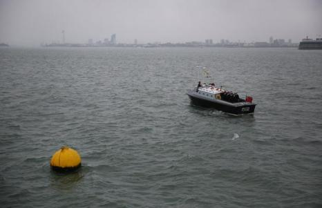 Моряки рядом с местом затопления корабля, обозначенным жёлтым буем. Фото: Peter Macdiarmid/Getty Images