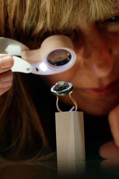 Ювелир Суси Хайнс (Susi Hines) смотрит на сделанное ею вращающееся армиллярное кольцо из 18-каратного золота и оксидированного серебра на выставке украшений и других изделий из драгоценных металлов Goldsmiths' Fair 23 сентября 2013 года в Лондоне. Фото: Matthew Lloyd/Getty Images