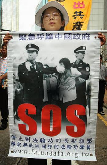 12 лет последователи Фалуньгун  Гонконге, указывают на преследование Фалуньгун в Китае. Многие люди подписывают их петиции за справедливость.  Фото: Mike Clarke/AFP/Getty Images