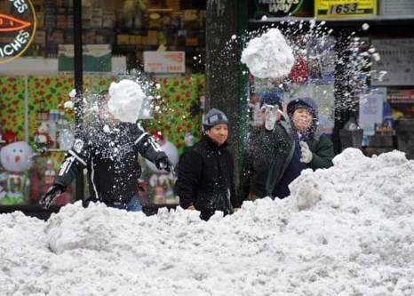 Двое мужчин пытаются расчистить груду снега на Третьей Авеню в Манхэттане в Нью-Йорке 28 декабря 2010. Фото: STAN HONDA/AFP/Getty Images