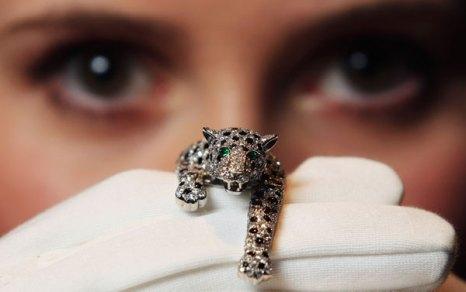 Служащая Сотбис держит фигурку пантеры из оникса и алмазов, созданную Картье в 1952 г.  Фото: Dan Kitwood/Getty Images