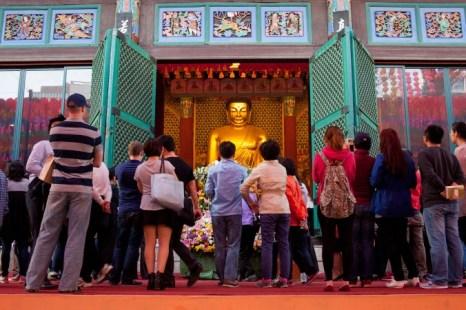 Верующие и гости собираются вокруг главной статуи Будды в храме Jogye в центре Сеула. Храм Jogye был основан в 1395 году, он является главным храмом. Фото: Jarrod Hall/Великая Эпоха (The Epoch Times)