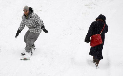 Зимой не до скуки. Сноубордист и прохожая в центре Эшвилля, штат Северная Каролина, 10 января. Фото: Scott Halleran/Getty Images