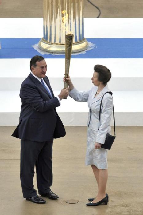 Церемония передачи Олимпийского огня «Лондона-2012» на стадионе «Панатинаикос» в Афинах, Греция.  Спирос  Капралос  (Spyros Capralos) передаёт Олимпийский факел принцессе Анне. Фоторепортаж. Фото: Milos Bicanski/Getty Images