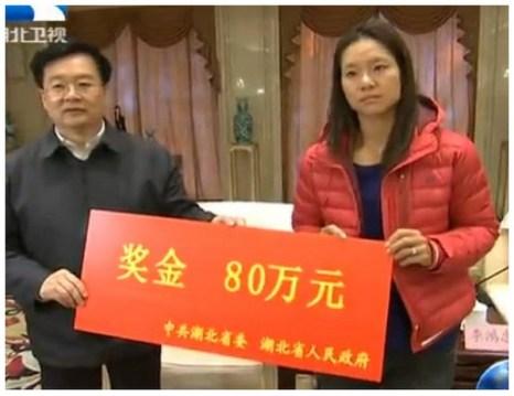Однако когда Ли На встретили на родине, и руководство компартии Китая вручило ей чек на 800 000 юаней, что примерно составляет 130 тысяч долларов США, она выглядела совсем безрадостной. Фото: Screenshot/HBTV via ECNS