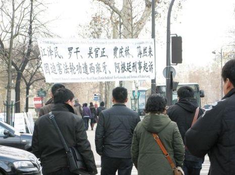 Группа китайских туристов остановилась возле баннера, обсуждая увиденное. Фото: Hao Yang/The Epoch Times