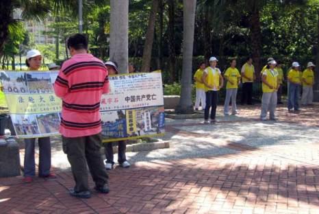 Китайский турист читает плaкат последователей Фалуньгун. Справа - демонстрация упражнений Фалуньгун. Фото: Великая Эпоха