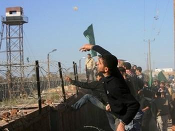 Палестинские демонстранты бросают камни в египетскую сторону на границе. Египетский солдат был убит и десятки палестинцев ранены в демонстрациях протеста против стального забора, возводимого Египтом в Рафиахе. Фото: Мохаммед Абед, Агентство Франс Пресс.