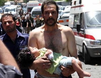 Сирийский мужчина несёт раненую девочку 8 июня 2012 года. Фото: -/AFP/GettyImages
