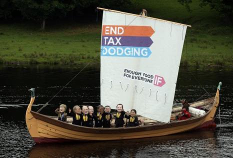Протестующие запустили по реке лодку с куклами, имитирующими глав Большой восьмёрки. На парусе лодки написано «Конец уклонению от налогов, если еды достаточно для всех». Фото: Matt Cardy/Getty Images