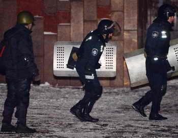 Милиционеры покидают здание Украинского дома на Европейской площади. Фото: SERGEI SUPINSKY/AFP/Getty Images