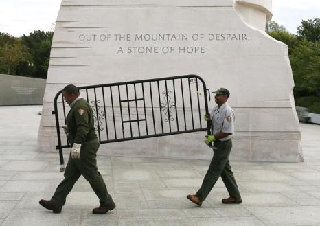 Рабочие несут баррикаду, которая закрывала памятник Мартину Лютеру Кингу во время выключения правительства, на следующее утро после принятия законопроекта о возобновлении работы правительства США 17 октября 2013 года. Фото: Mark Wilson / Getty Images
