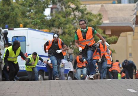 Добровольцы из азиатского сообщества бегут на помощь после того, как стала слышна очередная серия выстрелов в торговом центре в Найроби, 23 сентября 2013 года. Фото: TONY KARUMBA/AFP/Getty Images