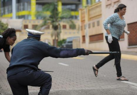 Кенийский полицейский волонтёр прикрывает людей после того, как стала слышна очередная серия выстрелов в торговом центре в Найроби, 23 сентября 2013 года. Фото: TONY KARUMBA/AFP/Getty Images