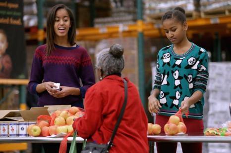 Дочери Барака Обама Малия и Сашя приняли участие в раздаче еды нуждающимся 27 ноября 2013 года в Банке продовольствия Вашингтона. Фото: Chip Somodevilla/Getty Images