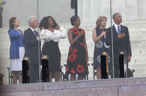 Президент Барак Обама, Кэролайн Кеннеди, первая леди Мишель Обама, Опра Уинфри, бывший президент Билл Клинтон и Линда Берд Джонсон Робб слушают национальный гимн на церемонии, посвящённой 50-летию со дня исторического «Марша Вашингтона», 28 августа 2013 года на Мемориале Линкольна в столице США. Фото: Alex Wong/Getty Images