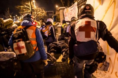 Медработники Майдана эвакуируют раненых демонстрантов в ходе столкновения с милицией на улице Грушевского, возле стадиона
