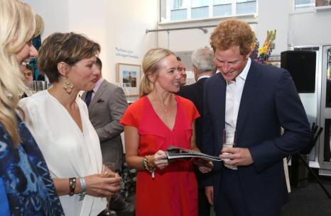 Принц Гарри встречает гостей на закрытом показе благотворительной фотовыставки «Sentebale — истории надежды» в галерее Getty Images 25 июля 2013 года в Лондоне, Великобритания. Фото: Tim P. Whitby/Getty Images