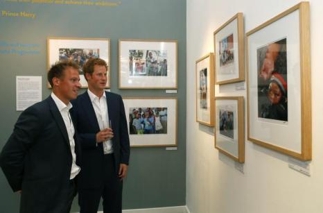 Автор фотографий выставки Крис Джексон (слева) и принц Гарри (справа) на закрытом показе благотворительной фотовыставки «Sentebale — истории надежды» в галерее Getty Images 25 июля 2013 года в Лондоне, Великобритания. Фото: Andrew Winning - WPA Pool/ Getty Images
