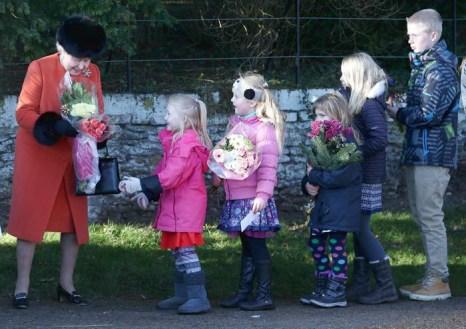 Королева Великобритании Елизавета II принимает цветы от детей во время поездки в Сандрингем 25 декабря 2013 года. Фото: Chris Jackson / Getty Images