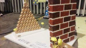 Пятьдесят пять яиц, каждое со своим уникальным «лицом», уложены в аккуратный «треугольник Паскаля», стоящего на одной стороне куска пенопласта. Две красно-коричневые кирпичные «стены» стоят на небольшом расстоянии от яиц, блокируя их «путь».