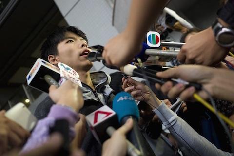 Студенческий лидер Джошуа Вон общается с журналистами у здания суда после того, как был выпущен под залог 27 ноября 2014 года. Суд Гонконга запретил лидеру движения за демократию посещать городской район, где накануне его арестовали полицейские, прибывшие очистить место от протестующих. Фото: Aaron Tam/AFP/Getty Images