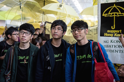Студенческие лидеры Алекс Чоу (в центре), Натан Лав (слева) и Исон Чун (справа), окружённые протестующими сторонниками демократии, в международном аэропорту Гонконга. Они планировали вылететь в Пекин, 15 ноября 2014 года. Фото: Alex Ogle/AFP/Getty Images