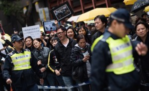 Демонстранты разговаривают с офицером во время марша против жестокости полиции в районе Wan Chai 7 декабря 2014 года, Гонконг. Фото: Johannes Eisele/AFP/Getty Images