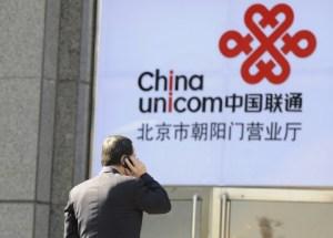 Офисный работник говорит по мобильному телефону на фоне логотипа China Unicom в Пекине 5 января 2012 года. Компанию сейчас проверяют антикоррупционные органы. Фото: Liu Jin/AFP/Getty Images