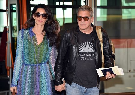 "US movie star George Clooney (R), accompanied by his wife Amal (L), arrives at Haneda airport in Tokyo on May 24, 2015. Clooney is now here for the Japanese premiere of his new film ""Tomorrowland"", a retro-futuristic spectacle mixing environmental themes with sci-fi wizardry.        AFP PHOTO / Yoshikazu TSUNO        (Photo credit should read YOSHIKAZU TSUNO/AFP/Getty Images)"
