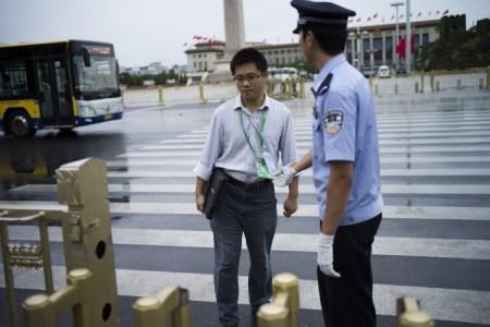Китайский полицейский проверяет прохожих при входе на площадь Тяньаньмэнь в Пекине 1 сентября 2015 года. Перед военным парадом 3 сентября в стране были приняты крайние меры безопасности