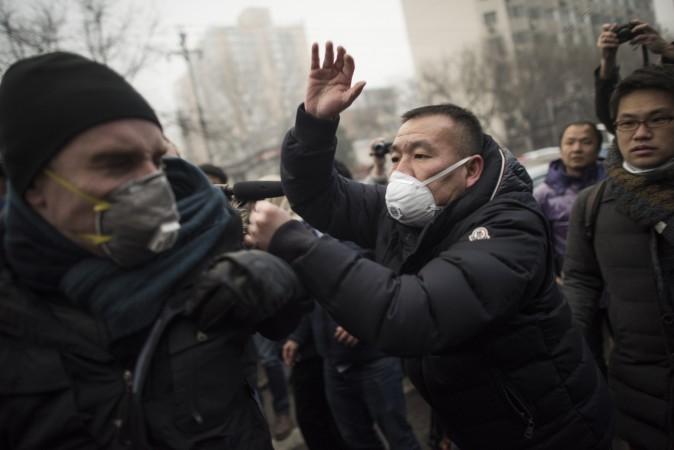 Китайская милиция растолкала и швырнула на землю журналистов и протестующих, собравшихся у здания пекинского суда перед процессом над известным адвокатом Пу Чжицяном 14 декабря 2015 г. Фото: Fred Dufour/AFP/Getty Images