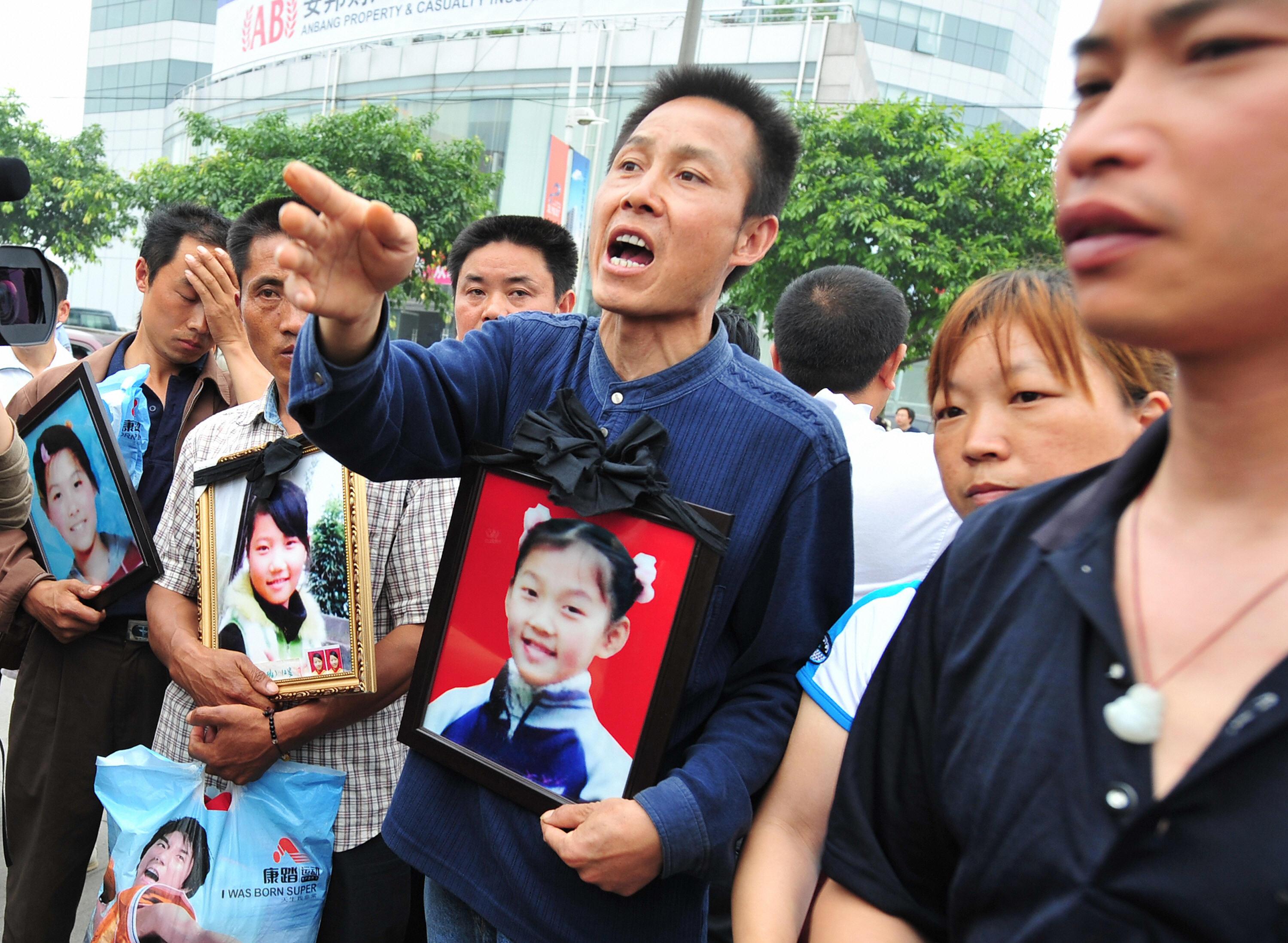 Скорбящие родители держат портреты погибших детей во время протеста в Дэяне 25 мая 2008 г. Фото: Frederic J. Brown/AFP/Getty Images