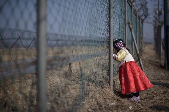 Девочка в традиционной корейской одежде Ханбок смотрит сквозь ограду в демилитаризованной зоне, разделяющую Южную и Северную Корею 19 февраля 2015 г. Фото: Ed Jones/AFP/Getty Images