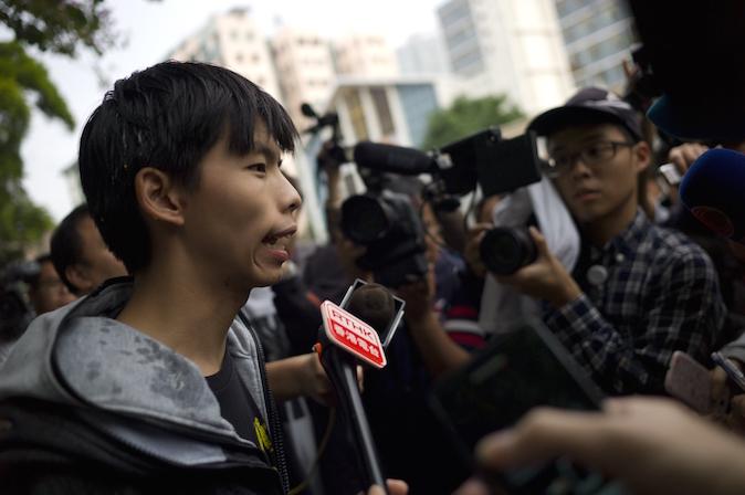 Студенческий лидер Джошуа Вон (слева) беседует с журналистами после того, как в него бросили яйца возле здания суда в Гонконге 27 ноября 2014 года. Фото: Aaron Tam/AFP/Getty Images