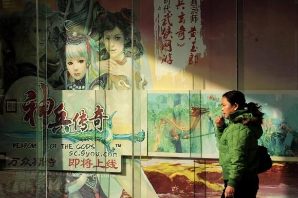 Женщина проходит мимо рекламного плаката с персонажами китайской онлайн-игры 7 декабря 2010 г. Фото: PHILIPPE LOPEZ/AFP/Getty Images