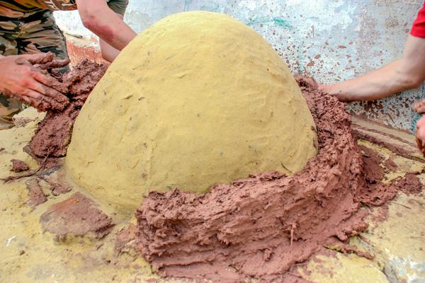Укладка самана вокруг песочной формы. Фото: Алла Лавриненко/Великая Эпоха