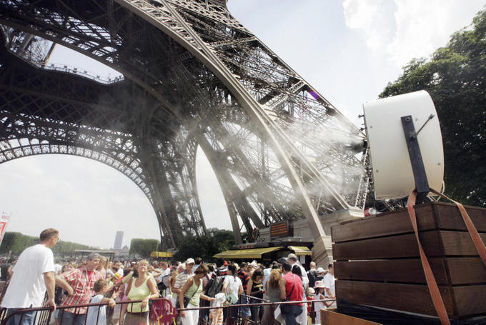 Гигантский спрей освежает посетителей Эйфелевой башни, спасая их от 36-градусной жары. Фото: FRANCOIS GUILLOT/AFP/Getty Images