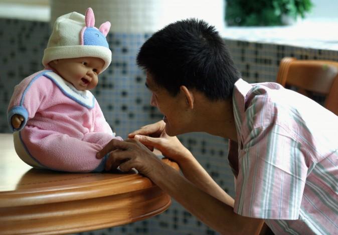 Китаец, страдающий от сенильной деменции, играет с куклой в реабилитационном центре Цихуй в Гуанчжоу, 2 сентября 2005 г. Фото: China Photos/Getty Images