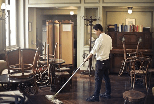 A man is seen mopping an epoxy floor as a daily routine.
