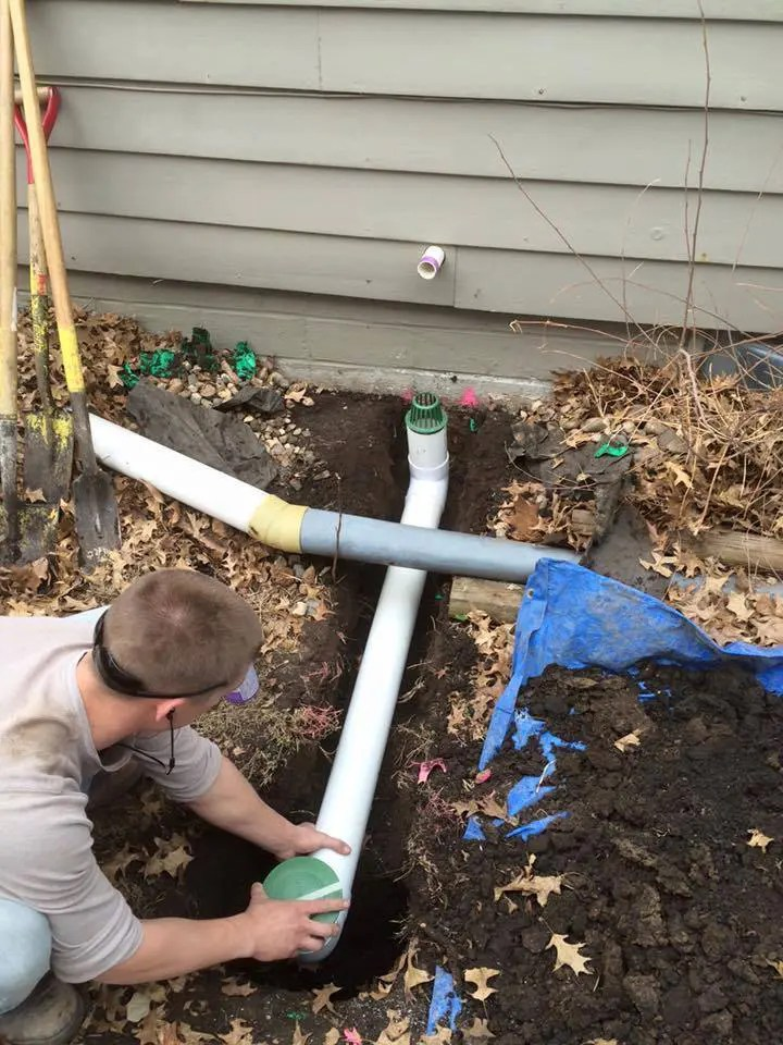 Man installing an exterior drainage system next to a house
