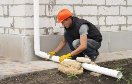 man installing a downspout extension