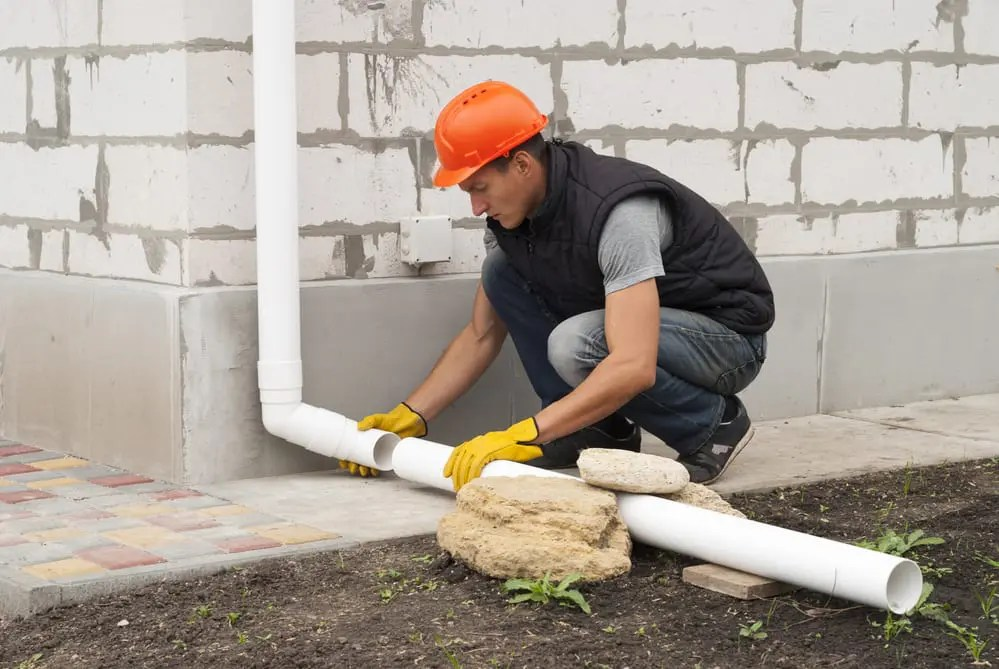 Photo of a man installing a downspout extension