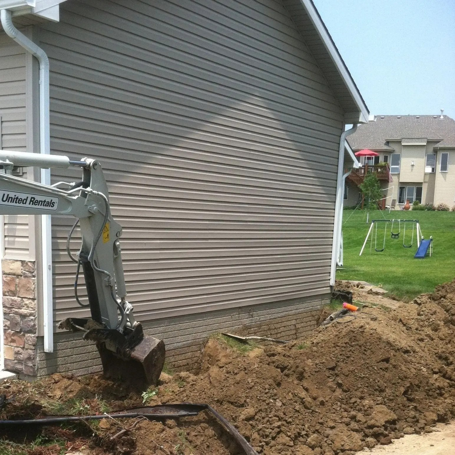Excavation in preparation for applying a foundation waterproofing membrane to a home's foundation