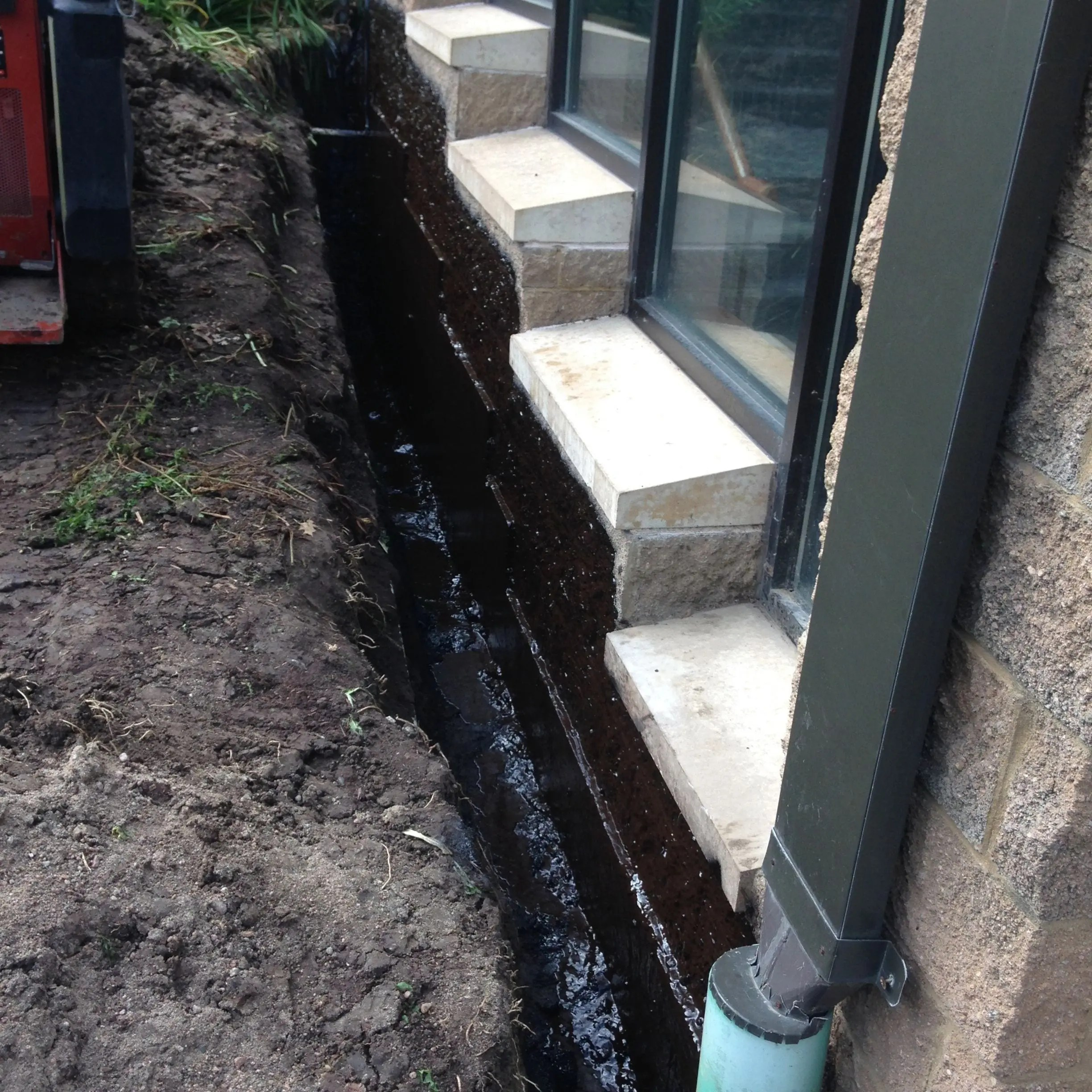 Applying a foundation waterproofing membrane to a building's foundation