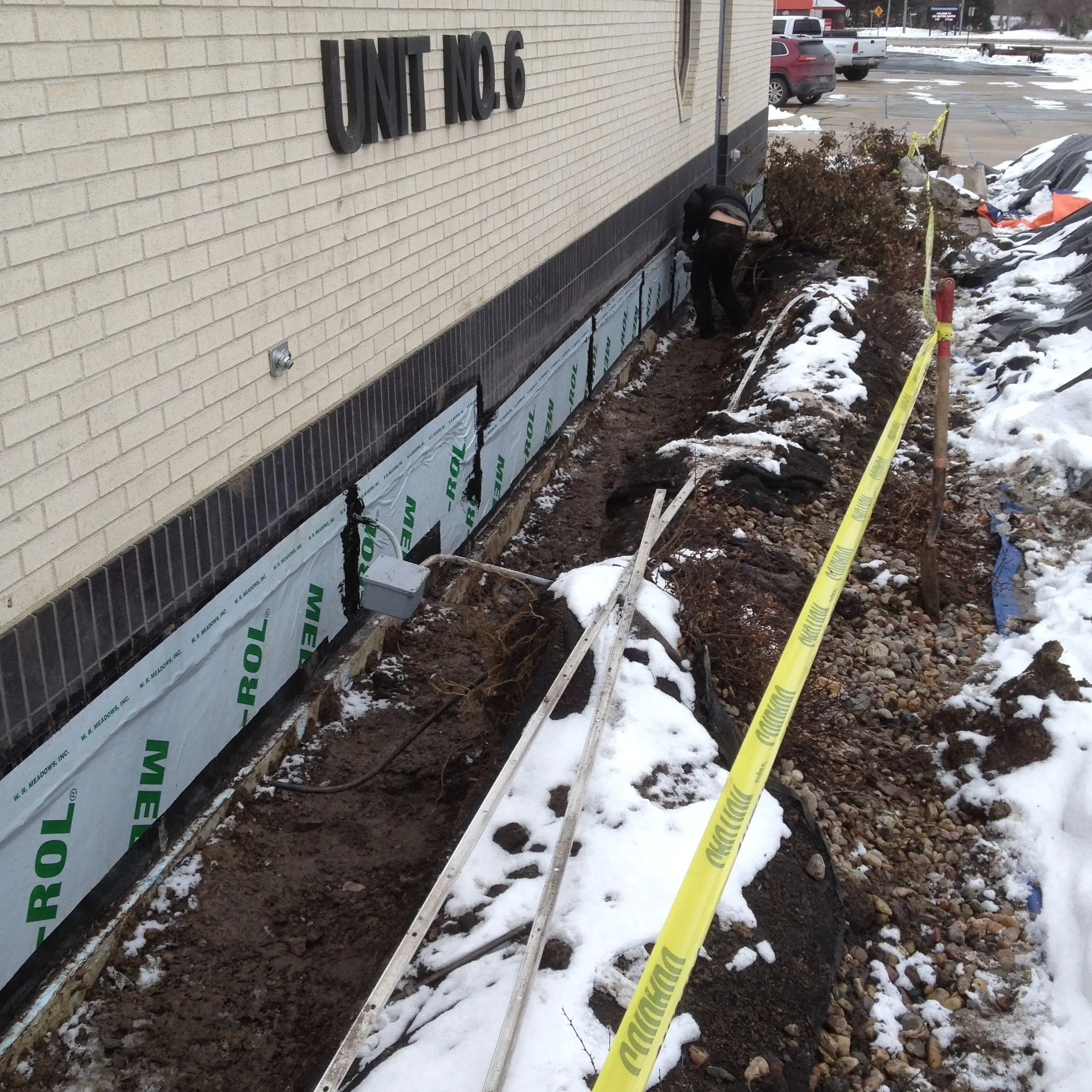 Applying a foundation waterproofing membrane to a home's foundation