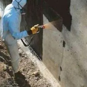A man applying a foundation waterproofing membrane to a foundation