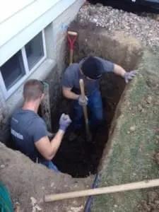Two men installing a basement egress window